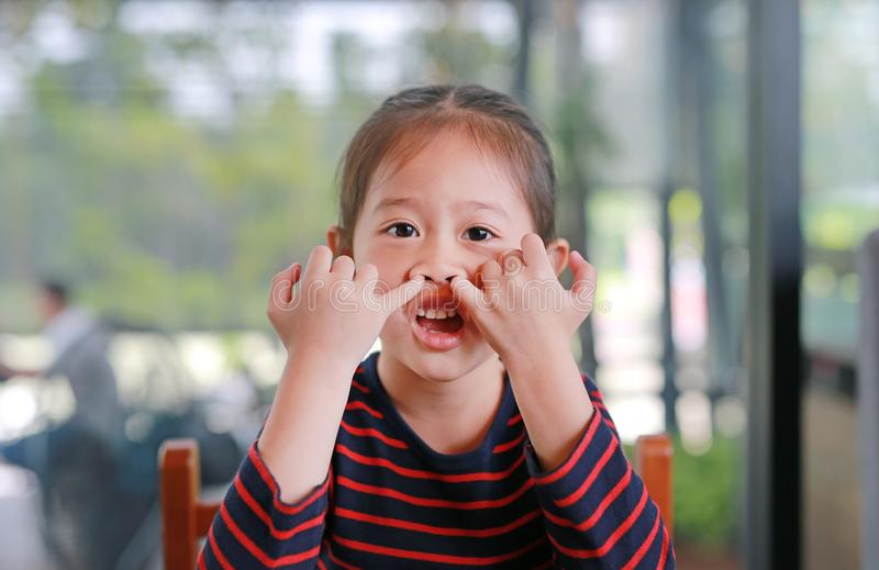 Sassy little Asian kid girl with pokes a finger in the nose royalty free stock images