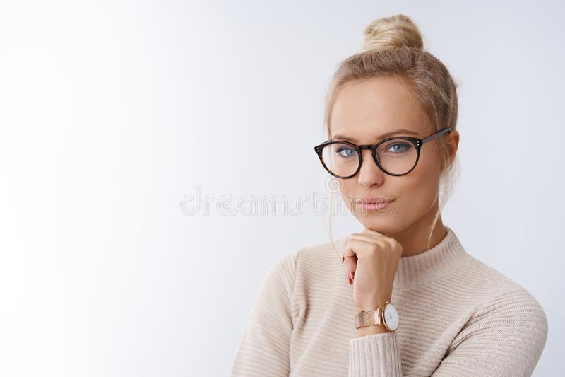 Sassy and successful good-looking accomlished female lifestyle blogger in glasses with blond hair combed holding fists stock photography
