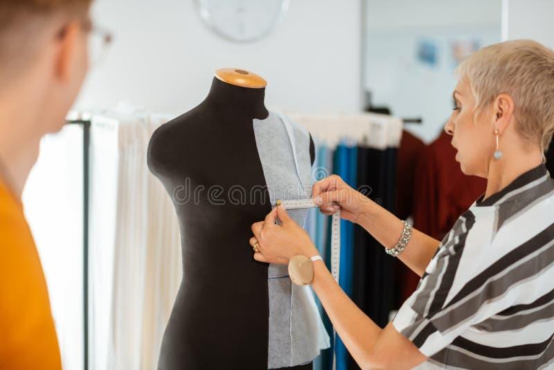 Sastre de sexo femenino concentrado mayor que mide la anchura del pecho imágenes de archivo libres de regalías