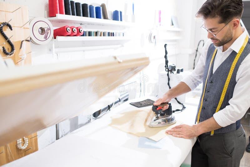 Sastre de sexo masculino Ironing Clothes en taller foto de archivo libre de regalías