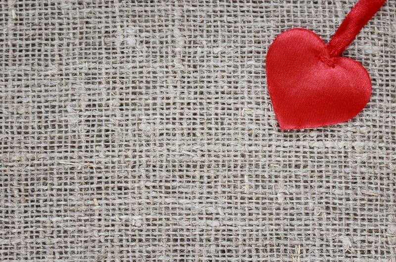 satén fácil del corazón blando que miente en una arpillera áspera imagenes de archivo