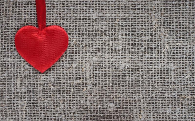 satén rojo fácil del corazón que miente en una arpillera áspera imágenes de archivo libres de regalías