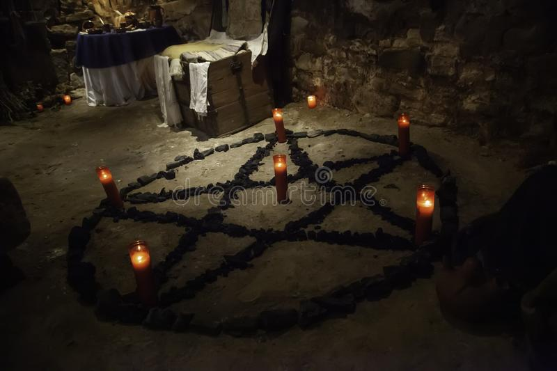 Satanic pentacle with lighted candles. Dark magic ritual detail, occultism stock image