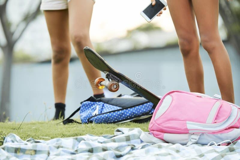 Satchels и скейтборд Schoolchildrens на траве стоковые изображения