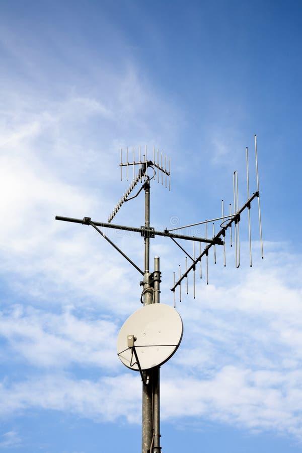 Satelliet schotel en dakantenne stock afbeelding