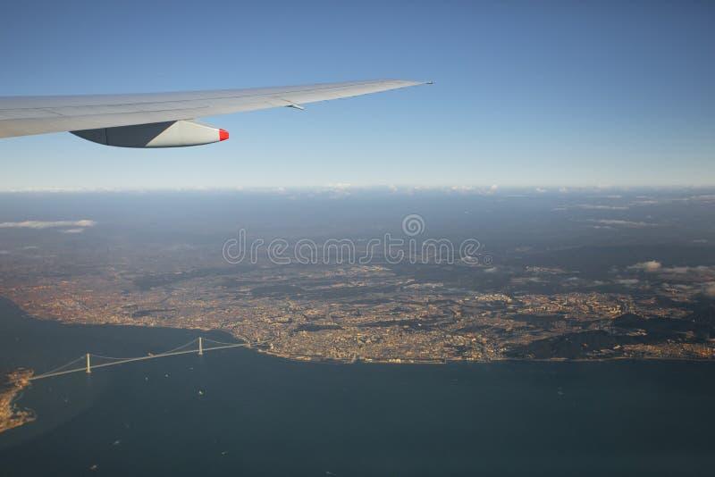 Satellietbeeld die van vliegtuigvenster over Brug akashi-Kaikyo de baai Japan kruisen van Osaka stock afbeelding