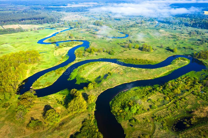Satellietbeeld op de zomerrivier Rivierstroom op groene weide Het landschap van de de zomeraard Hommelmening over rivieroever stock fotografie