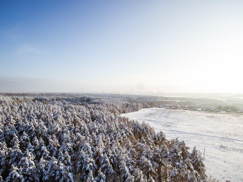 Satellietbeeld op gebied en de winterbos in sneeuw Dorp, daken na sneeuwval Vogelsoog van hommel royalty-vrije stock afbeeldingen