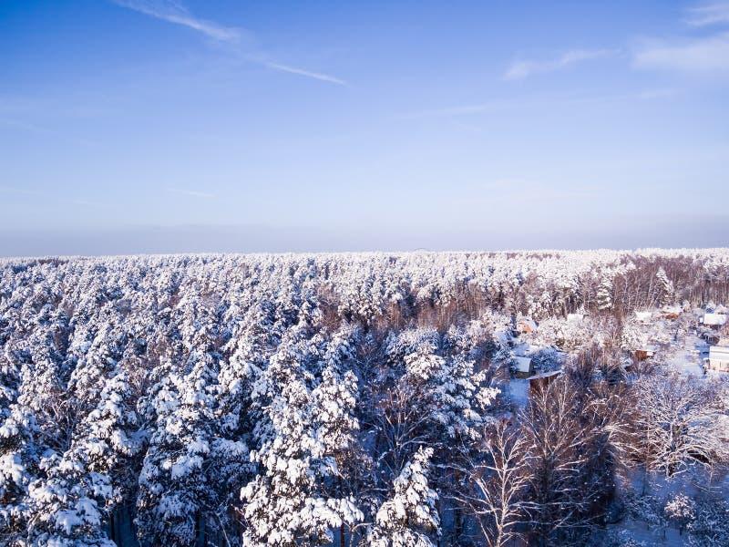 Satellietbeeld op het bos en het dorp van de sneeuwwinter Blauwe hemel op achtergrond De daken zijn onder de sneeuw stock afbeelding