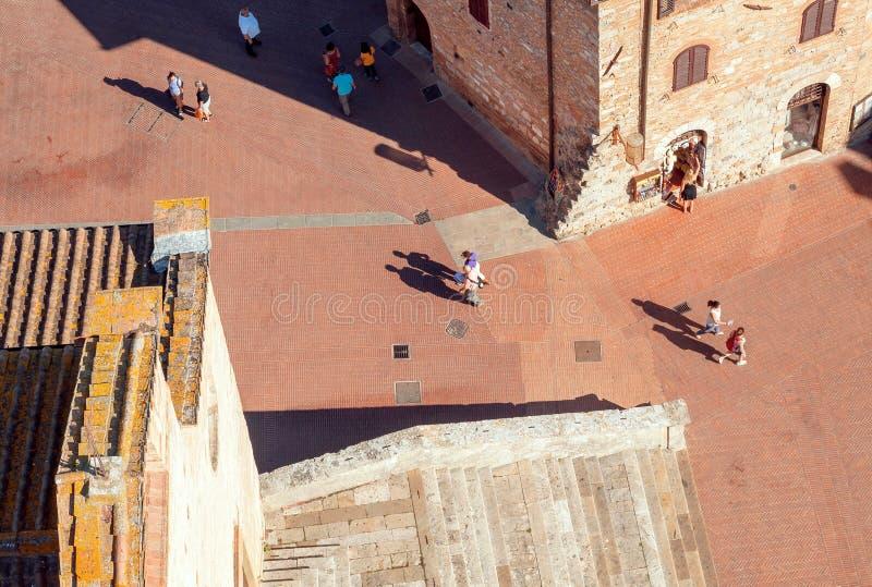 Satellietbeeld op middeleeuwse stad van Toscanië met baksteenhuizen en lopende mensen Italiaanse provincie stock foto's