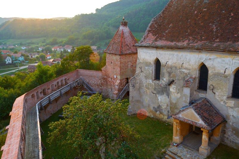 Satellietbeeld van Alma Vii versterkte kerk, met zongloed, bij zonsondergang Typisch vestingwerk in het gebied van Transsylvanië, royalty-vrije stock fotografie