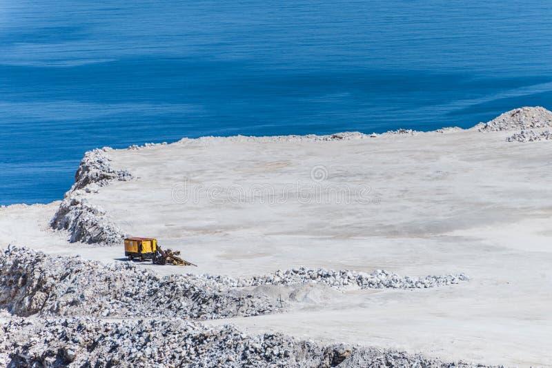 Satellietbeeld van bovengrondse mijnbouwsteengroeve met één machines op de blauwe overzeese achtergrond stock foto's