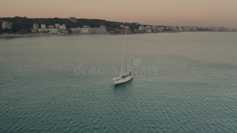 Satellietbeeld van een bewegende zeilboot dichtbij Nettuno in de avond, Italië stock foto's