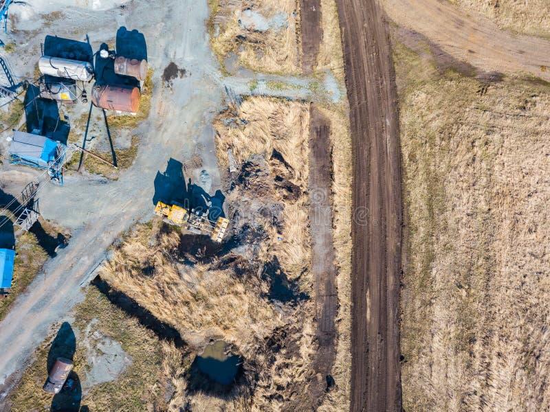 Satellietbeeld van een graafwerktuig en een gele tractor die verpletterd steen, cement en zand vervoeren tijdens de extractie van royalty-vrije stock afbeelding