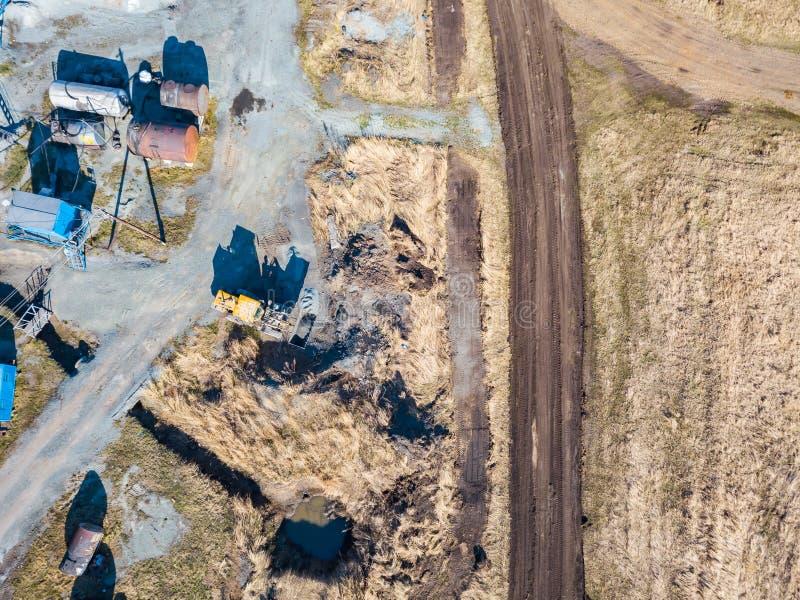 Satellietbeeld van een graafwerktuig en een gele tractor die verpletterd steen, cement en zand vervoeren tijdens de extractie van royalty-vrije stock foto