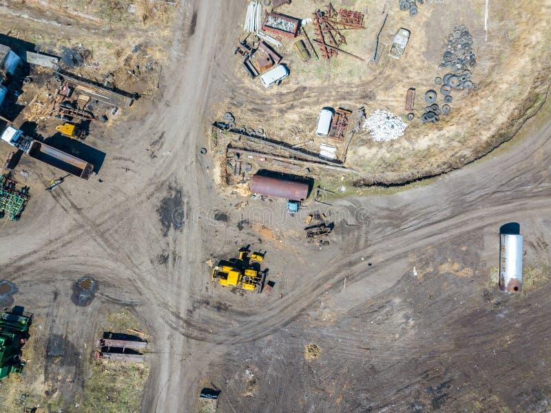 Satellietbeeld van een graafwerktuig en een gele tractor die verpletterd steen, cement en zand vervoeren tijdens de extractie van stock fotografie