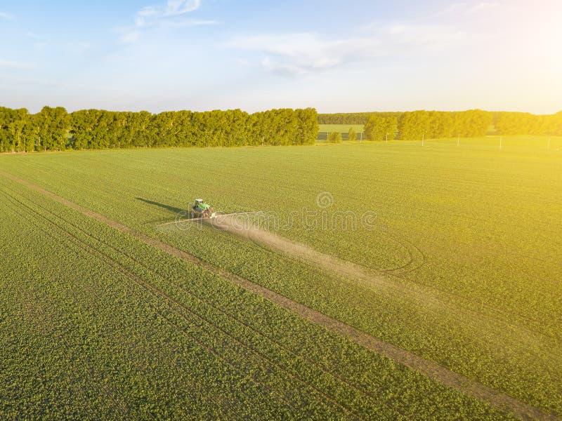Satellietbeeld van een landbouwbedrijftractor op een groen gebied tijdens het bespuiten en irrigatie met pesticiden en toxine voo royalty-vrije stock afbeelding