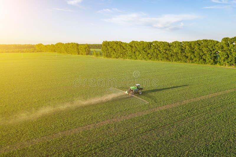Satellietbeeld van een landbouwbedrijftractor op een groen gebied tijdens het bespuiten en irrigatie met pesticiden en toxine voo royalty-vrije stock foto