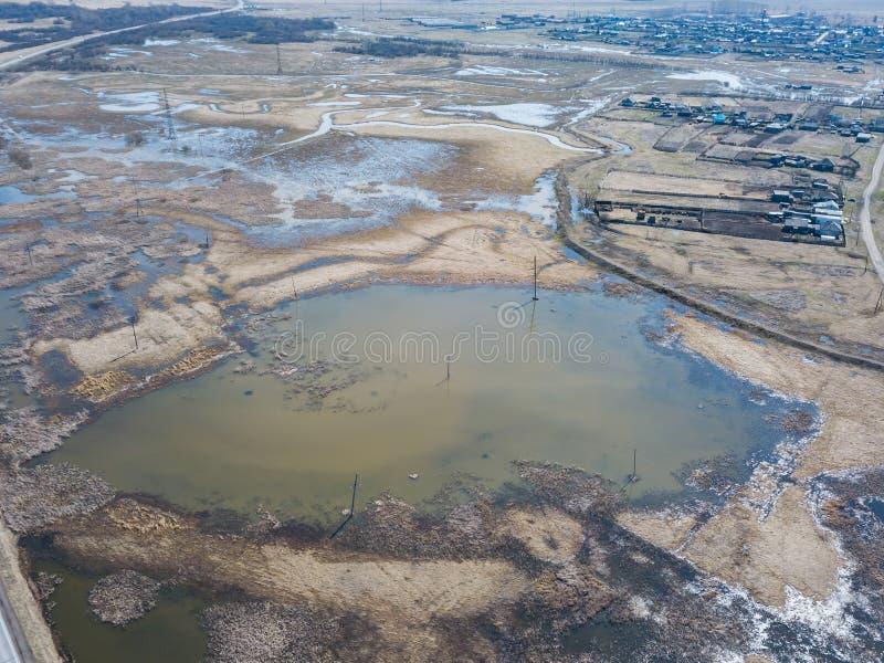 Satellietbeeld van een moerasland dichtbij een weg met een asfaltweg tijdens een de lentevloed, welke vloed en onduidelijke beeld stock afbeelding