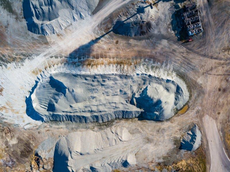 Satellietbeeld van een stapel van verpletterde steen en grijs cement dichtbij de installatie voor de productie van bouwmaterialen stock afbeelding