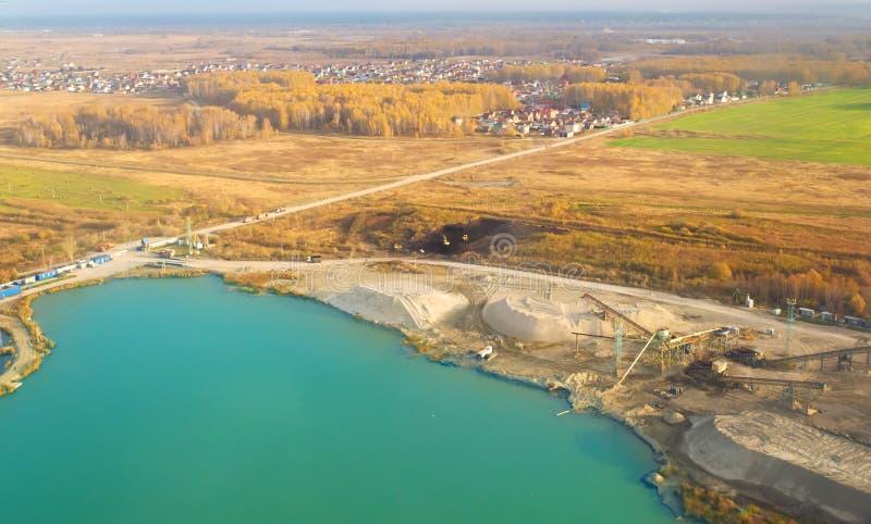 Satellietbeeld van een steengroeve van de zandmijnbouw op een turkoois meer met geposte bouwmateriaal en graafwerktuigen royalty-vrije stock afbeeldingen