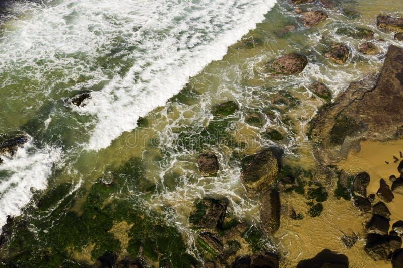 Satellietbeeld van golven die op rotsen at low tide breken stock afbeelding