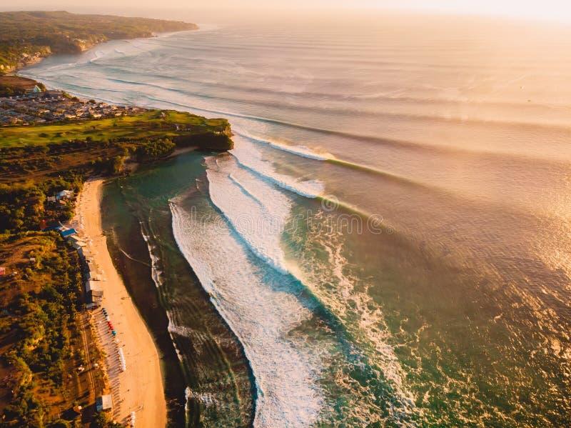 Satellietbeeld van grote golven voor het surfen bij warme zonsondergang en zandig strand Grootste oceaangolf in Bali royalty-vrije stock foto's