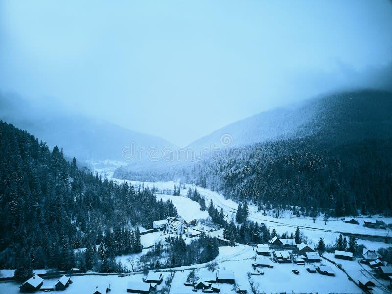 Satellietbeeld van mistig platteland en huizen in sneeuwvallei Heuvels en bergen met het bos van de pijnboomboom in sneeuw wordt  royalty-vrije stock afbeelding