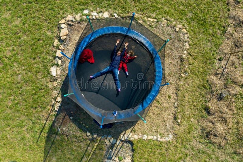 Satellietbeeld van moeder met haar dochter die pret op trampoline hebben door hommel stock fotografie