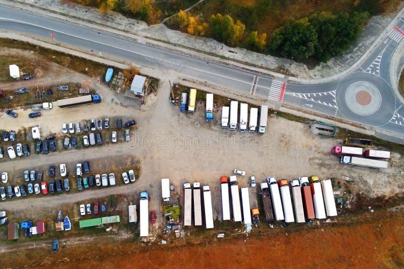 Satellietbeeld van ongeplaveid natuurlijk parkeren met veel vrachtwagens, aanhangwagens en auto's Rust plaats dichtbij weg en cir royalty-vrije stock afbeeldingen