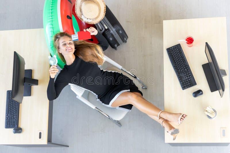 Satellietbeeld van Ontspannen bedrijfsvrouwenholding paspoort en het liggen op comfortabele bureaustoel in bureau Het concept van royalty-vrije stock afbeelding