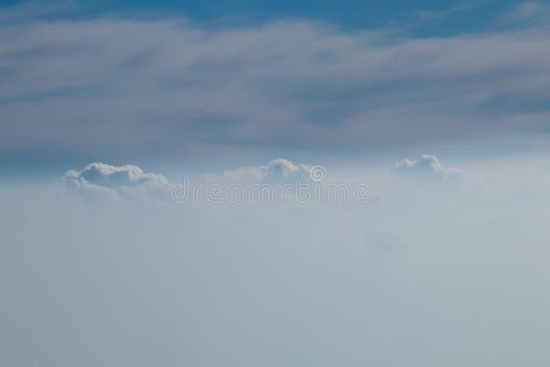 Satellietbeeld van vliegtuigvenster met blauwe hemel en witte wolken royalty-vrije stock fotografie