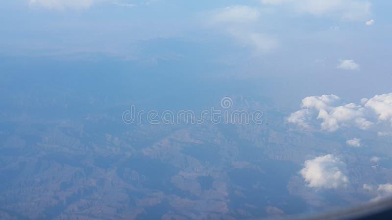 Satellietbeeld van vliegtuigvenster van mooie wolken en blauwe hemel royalty-vrije stock afbeelding