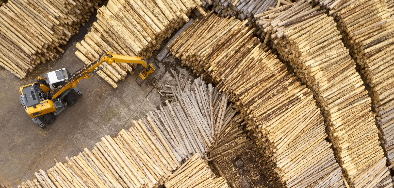 Satellietbeeld van zaagmolen en de gehakte stapels van het boom houten logboek op een rij met machines stock afbeelding