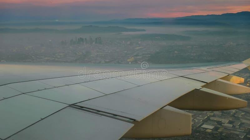 Satellietbeeld van zonsopgang en vliegtuigvleugel over Los Angeles stock fotografie