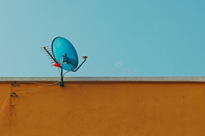 Satellietschotel en antenne met antennes om digitale TV en radiosignalen bovenop de bruine bouw te ontvangen royalty-vrije stock foto