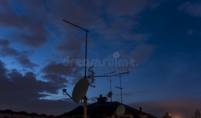 Satellietschotel en TV-antenne op dak bij schemer royalty-vrije stock afbeeldingen