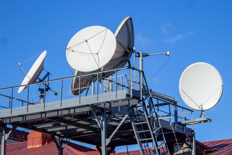 Satellietschotels op het dak van het gebouw, blauwe hemel, parabolische antenne royalty-vrije stock afbeelding
