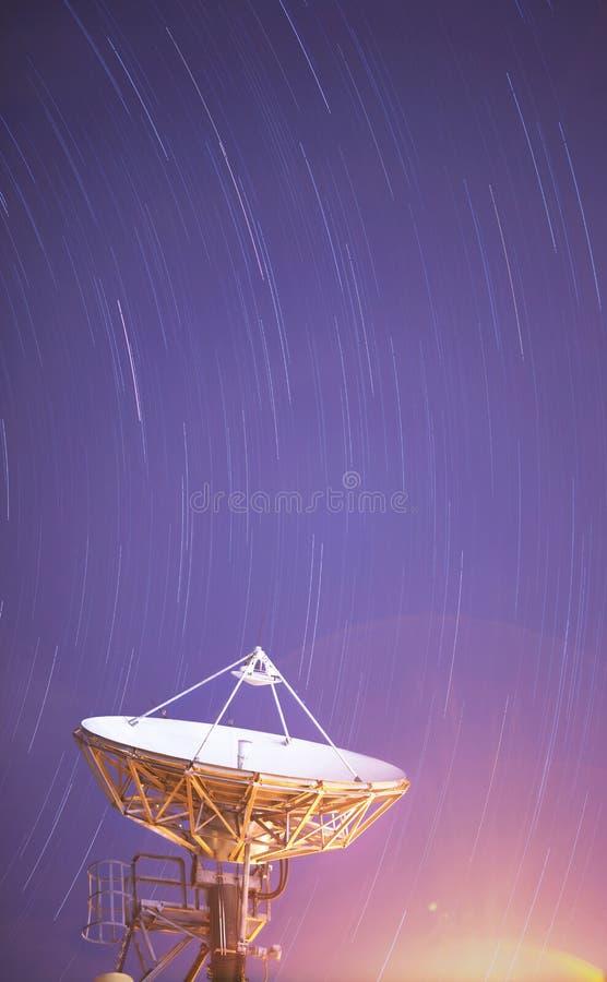 Satellit- antenn under startrailen arkivbild