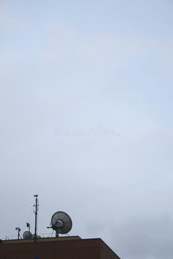 Satellit- disk och antenner på tak royaltyfri bild