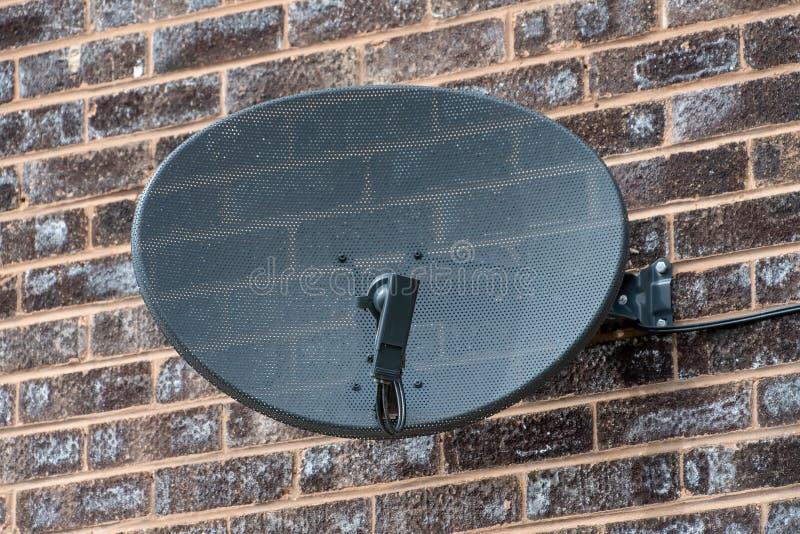 Satellit- maträtt för TV på en tegelstenvägg royaltyfri foto