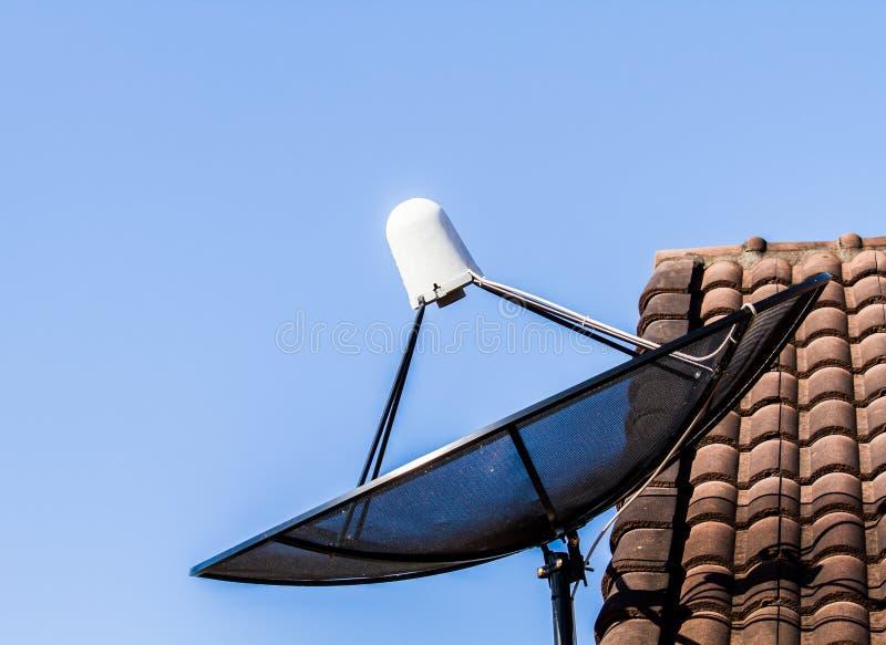 Satellit- maträtt på taket arkivfoton