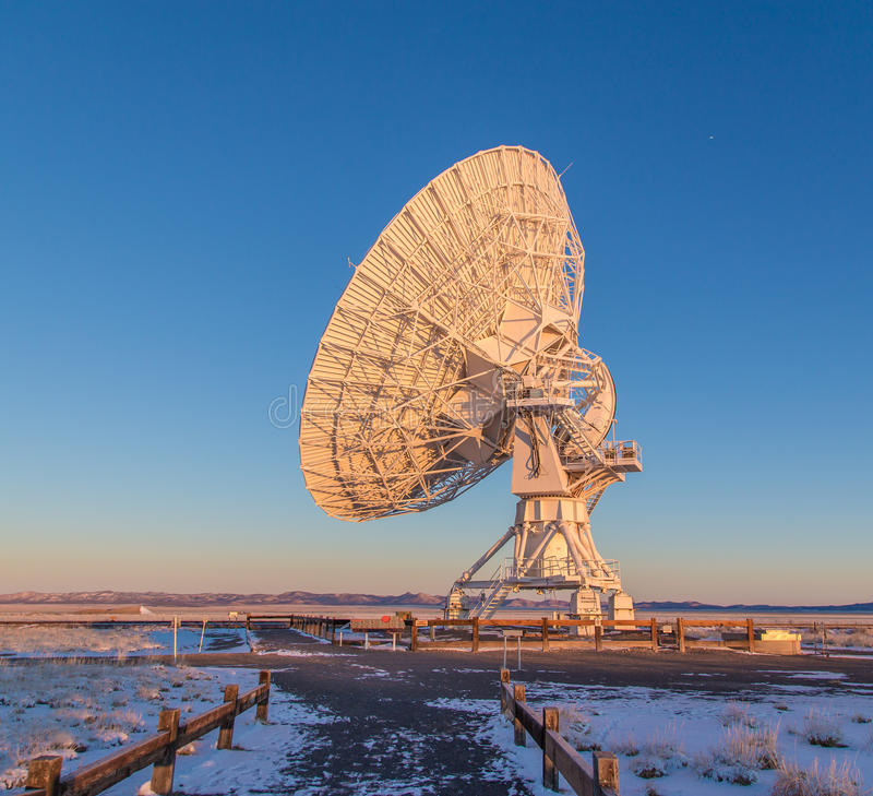 Satellite antenna dish. Side view of a large radio satellite antenna dish in a snowy countryside field stock image