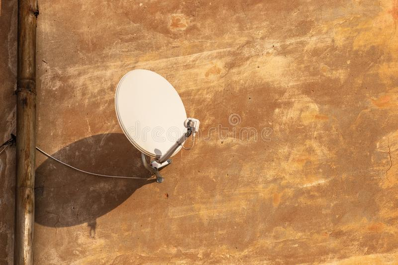 Satellite antenna for receiving digital TV signal on plastered wall stock photos