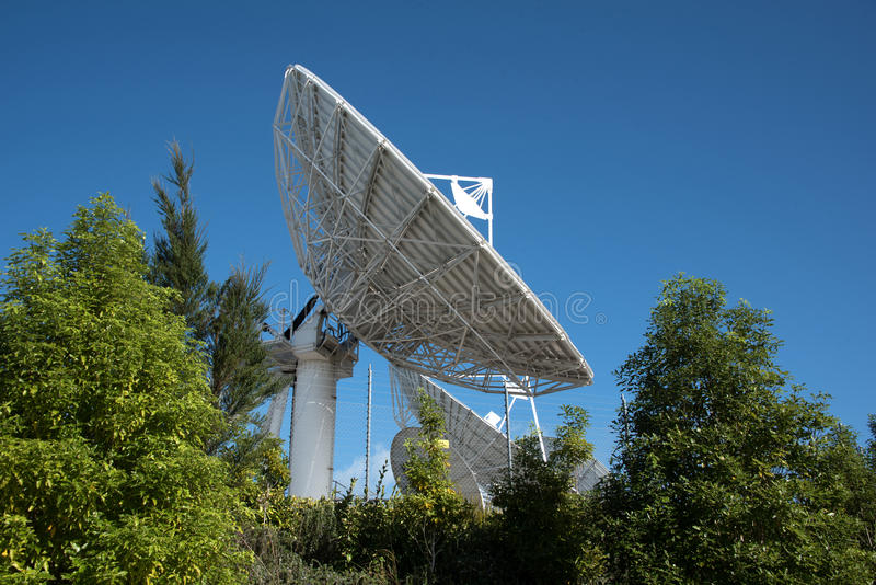 Satellite communication dish. Parabolic antenna designed to receive electromagnetic signals from satellites, which transmit data transmissions or broadcasts stock photography
