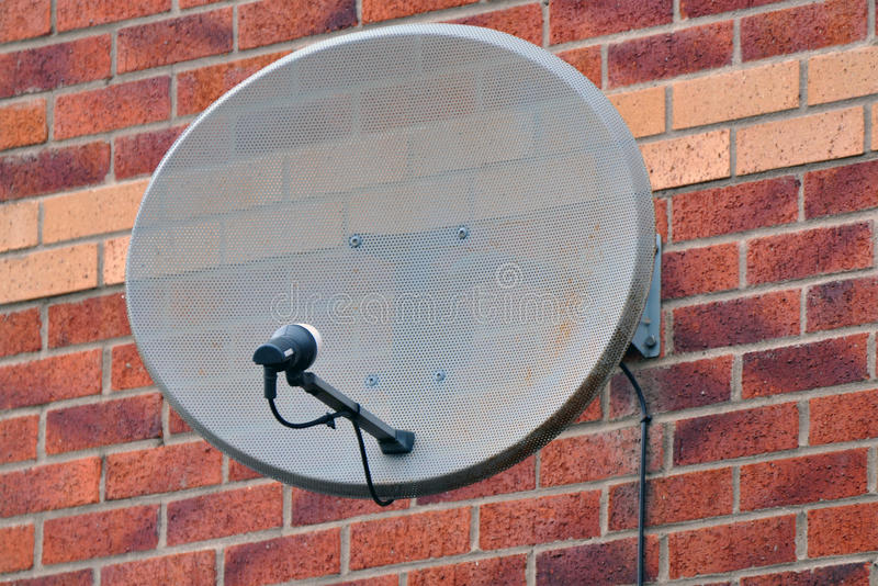 Satellite Dish. Satellite television dish mounted on a brick wall royalty free stock photography