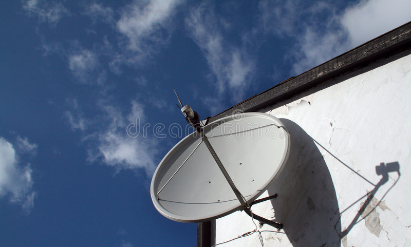 Satellite dish. For receiving sky or other satellite channels mounted on white wall with strong shadow of the LNB royalty free stock photography