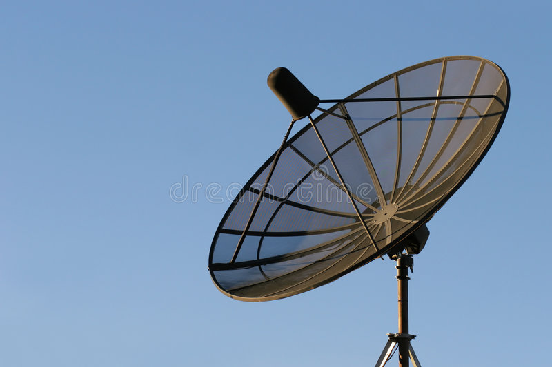 Satellite dish. Black dish mounted on a rooftop against clear blue sky stock images
