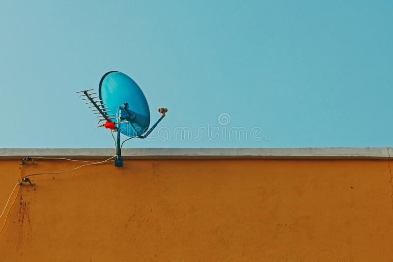 Satellite dish and antenna with antennas to receive digital TV and radio signals on top of brown building.. Satellite dish and antenna with antennas to receive royalty free stock photo