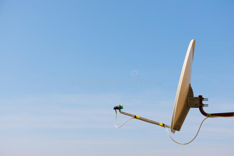 Satellite dish antenna for home TV over blue sky background stock images